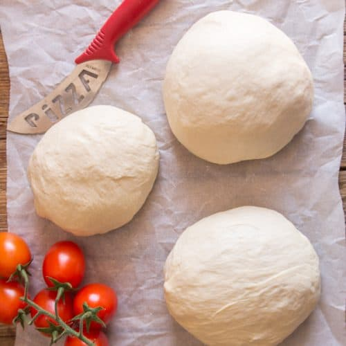 three-pizza-dough-balls-on-baking-paper